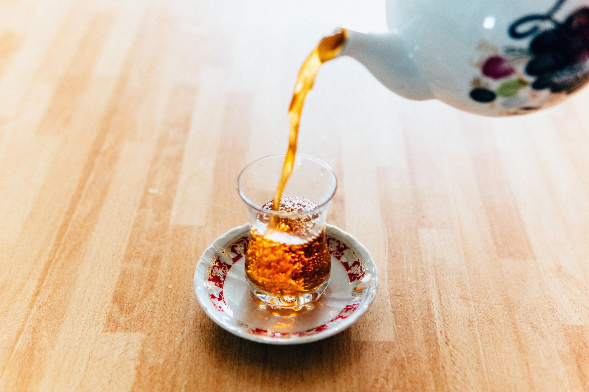 small shot glass being filled from teapot with dark liquid.