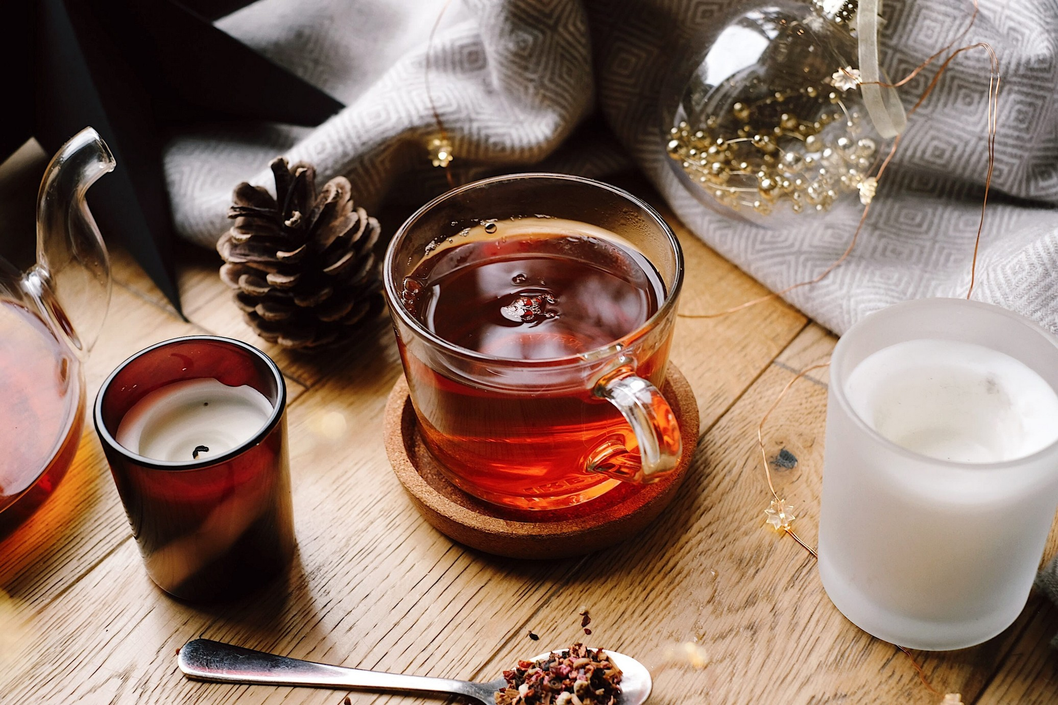 tea in glass mug with pine cones and candles scattered around.