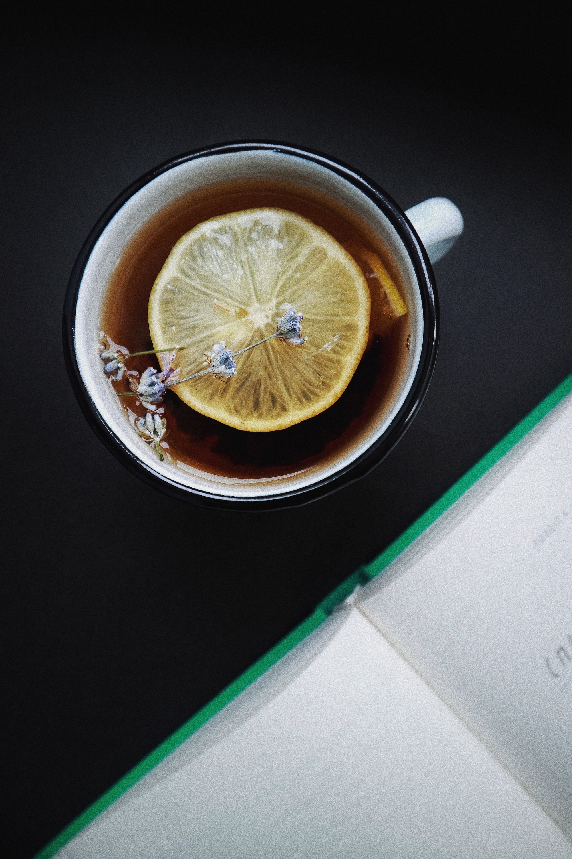 teacup with dark liquid and a slice of lemon sat next to an open notebook.