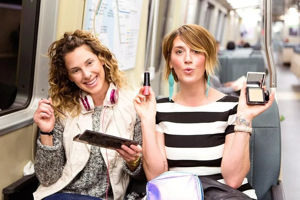 two women holding makeup products whilst on the tube.
