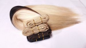 Hair extensions in different hair colors on a surface