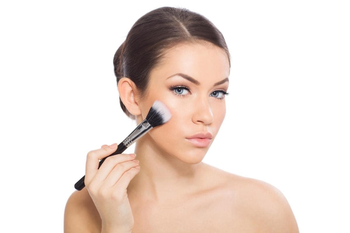 woman applying tinted moisturiser with a foundation brush.