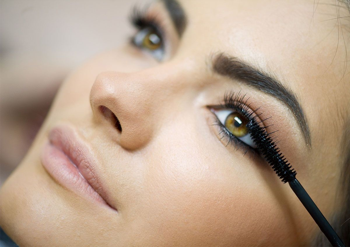 close up of woman having black mascara applied to her eyelashes.