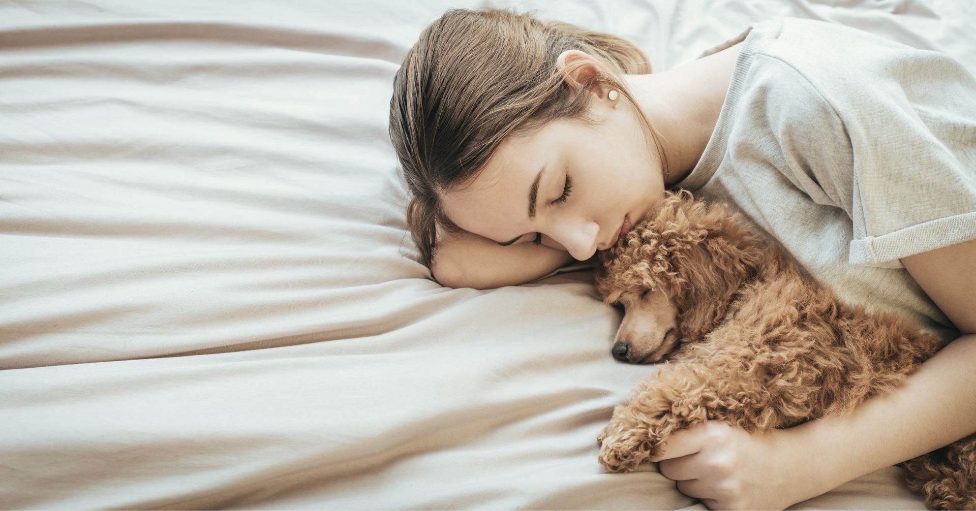 woman sleeping whilst holding a puppy between her arms.