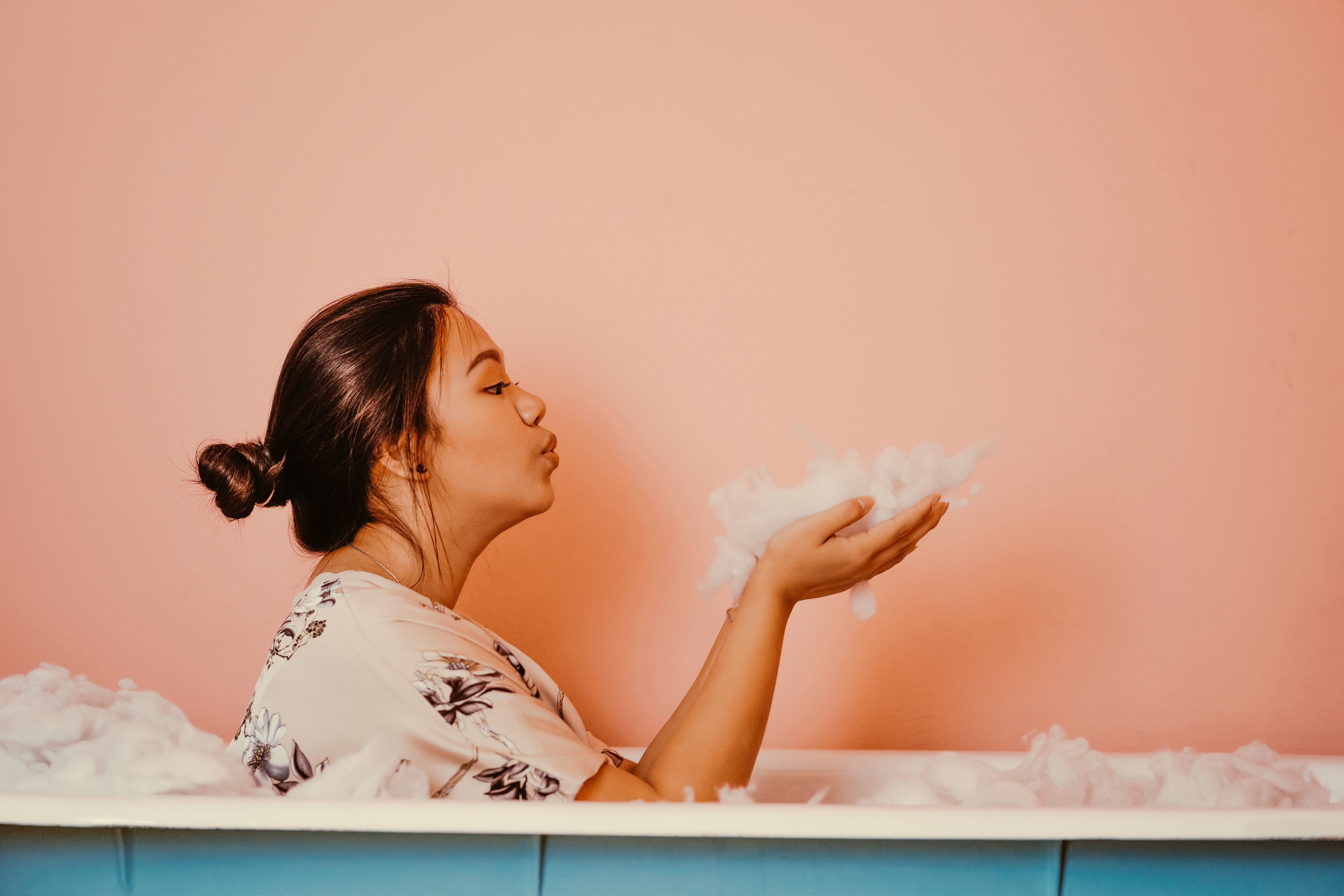 woman in a bath tub blowing bubbles and using body wash.