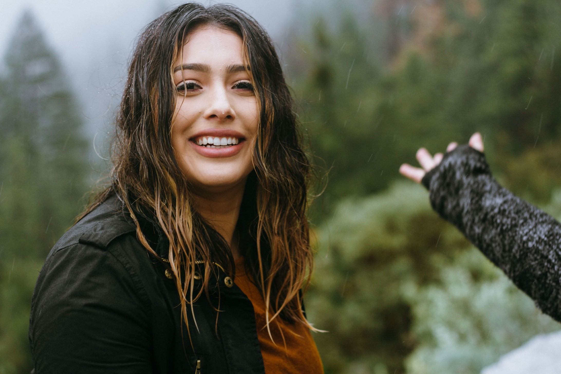 woman standing in the rain with wet hair, trees are pictured behind her.