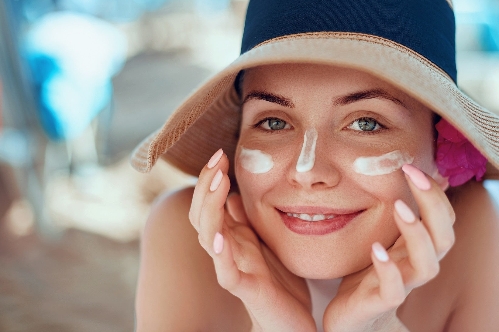 woman wearing a hat with sunscreen on her cheeks.