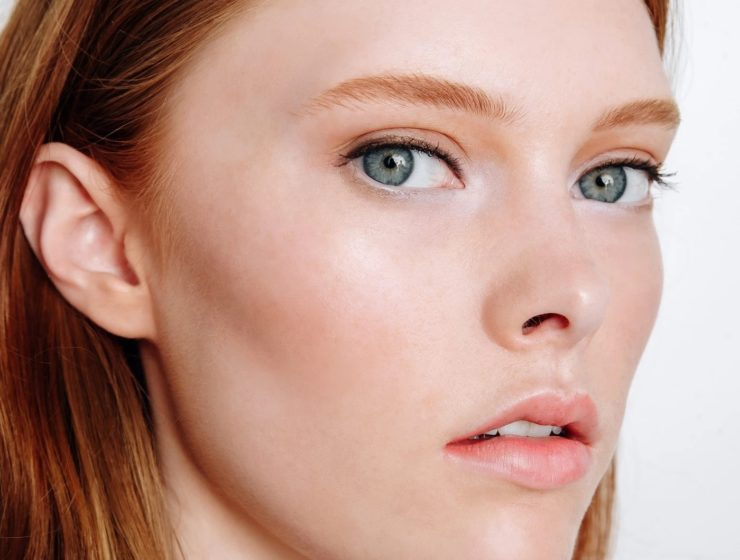 woman with auburn hair wearing tinted moisturizer.