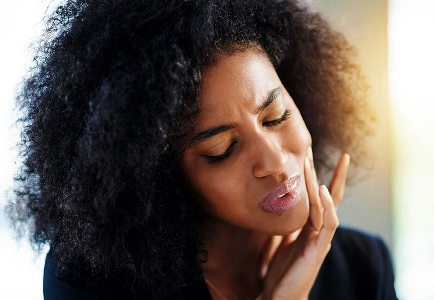 Facial Hair Removal: woman with paid expression touching her cheek.