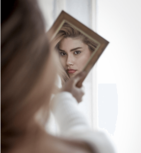 A woman looking in a mirror to determine what type of acne she has