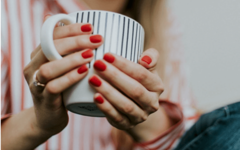 Woman wearing red nail polish and holding a mug
