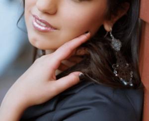 Woman wearing blush touching her cheek