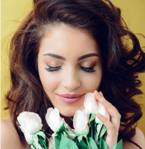 Woman wearing false eyelash extensions and holding flowers