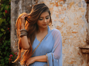 Woman with long, dyed hair wearing a blue sari