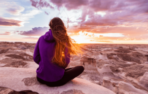 Woman with long brown and brass coloured hair sitting and watching a sunset