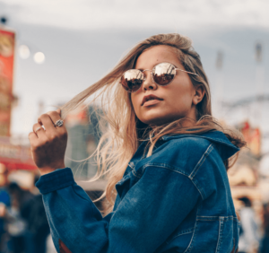 Woman with blond hair wearing a denim jacket and sunglasses holding a strand of her hair