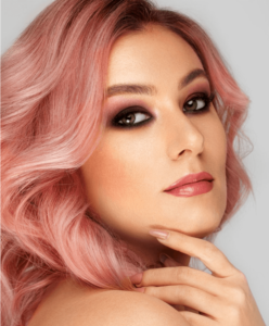 Woman with pink hair wearing makeup for dewy skin