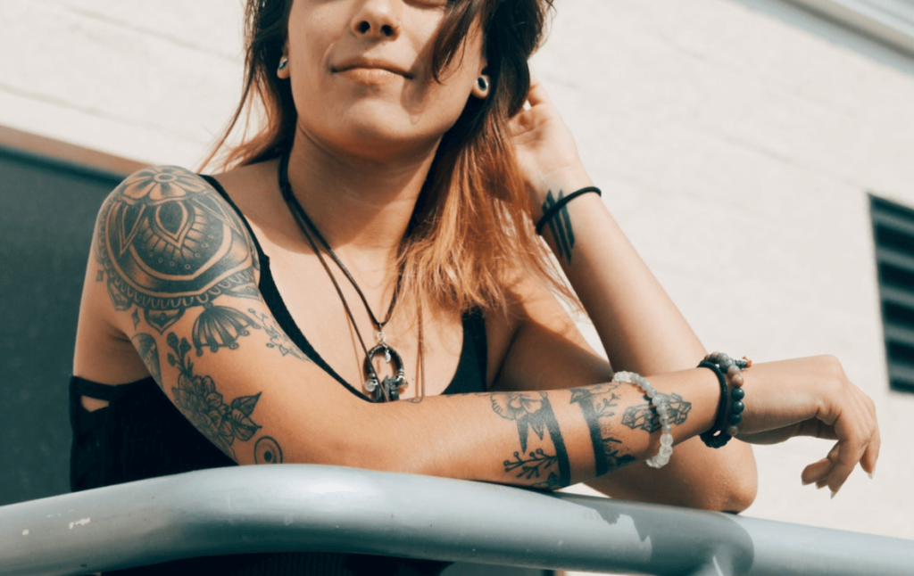 A woman with tattoos over her body standing on a balcony