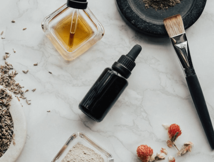 A bottle on essential oil near a makeup brush