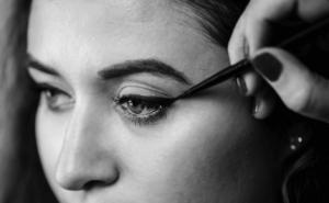 Woman applying liquid eyeliner to her eyelid