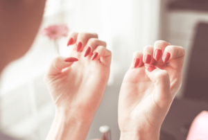 Woman looking at her freshly painted nails