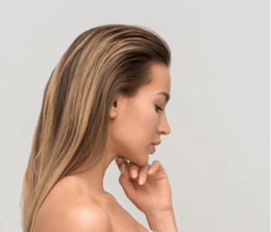 A woman with blonde hair touching her face