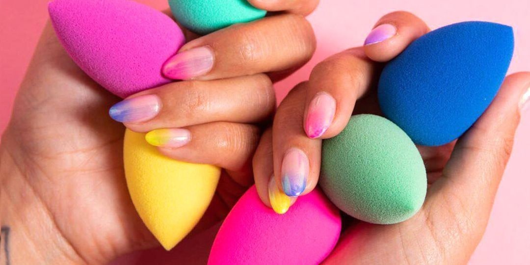 close up of a persons hands holding an array of colourful beauty blenders.
