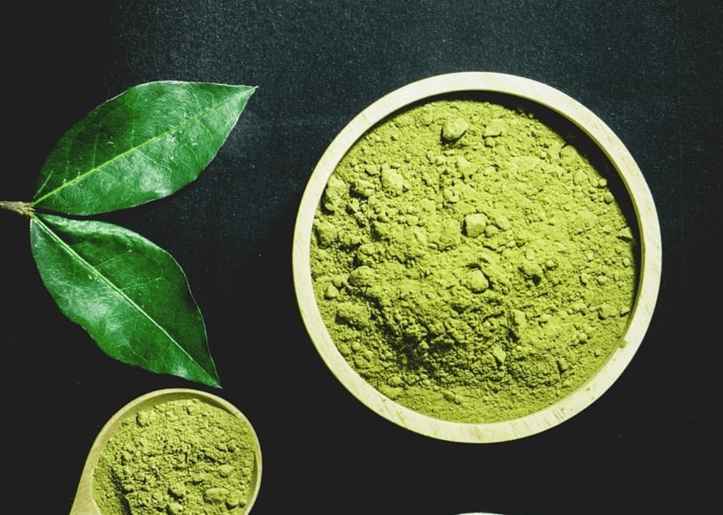 Green henna powder in a bowl with henna leaves near it.
