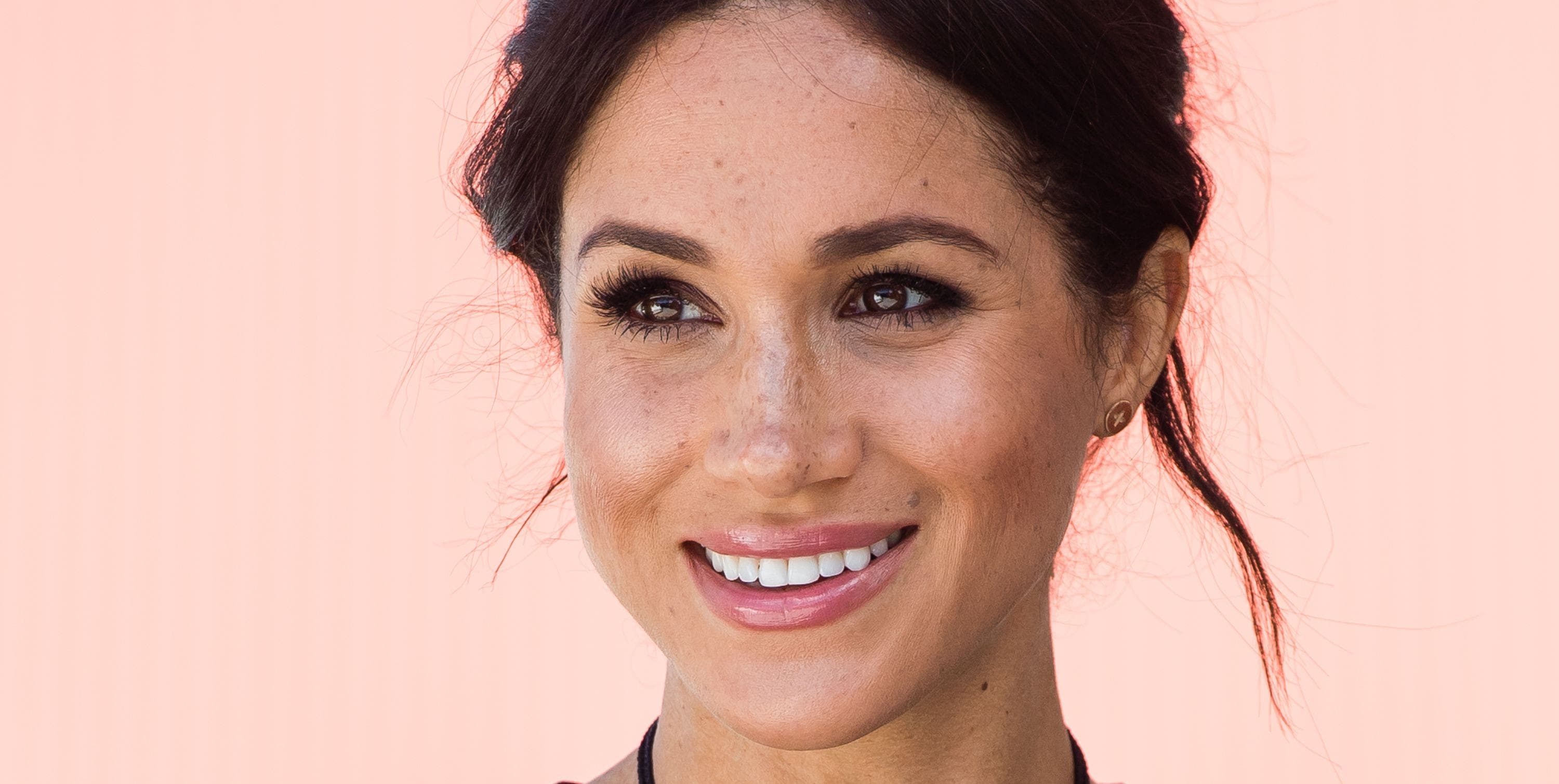 meghan markle smiling, displaying her facial freckles.