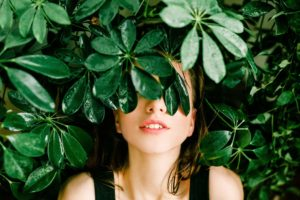 Woman standing under a bush of leaves with it covering her eyes