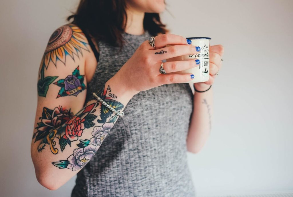 Woman with tattoos on her arm holding  a mug