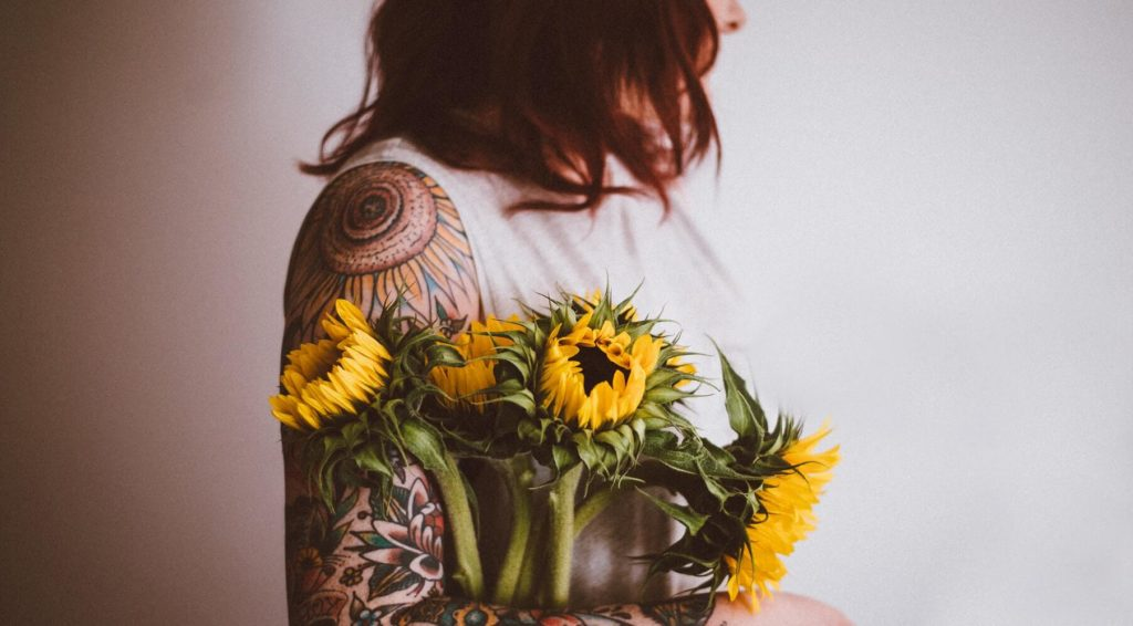 Woman with tattoos on her arm holding yellow flowers