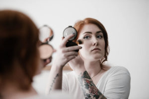 Woman applying blusher with a brush onto her face