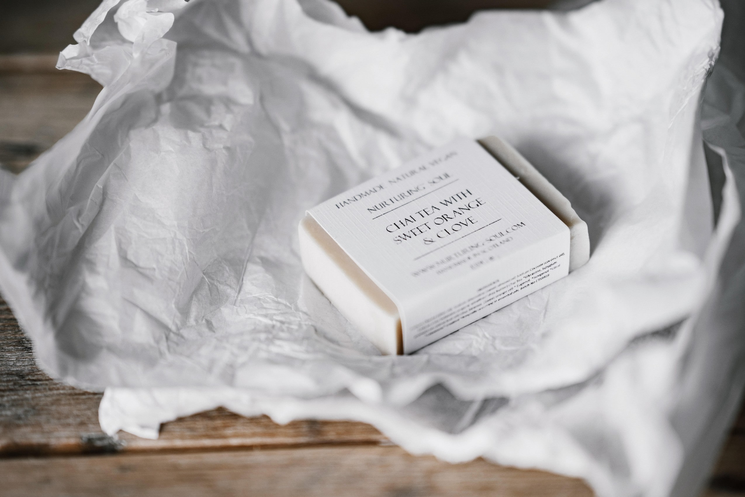 pictured is a bar of Chai Tea with Sweet Orange & Clove soap, laid on a crisp white paper.