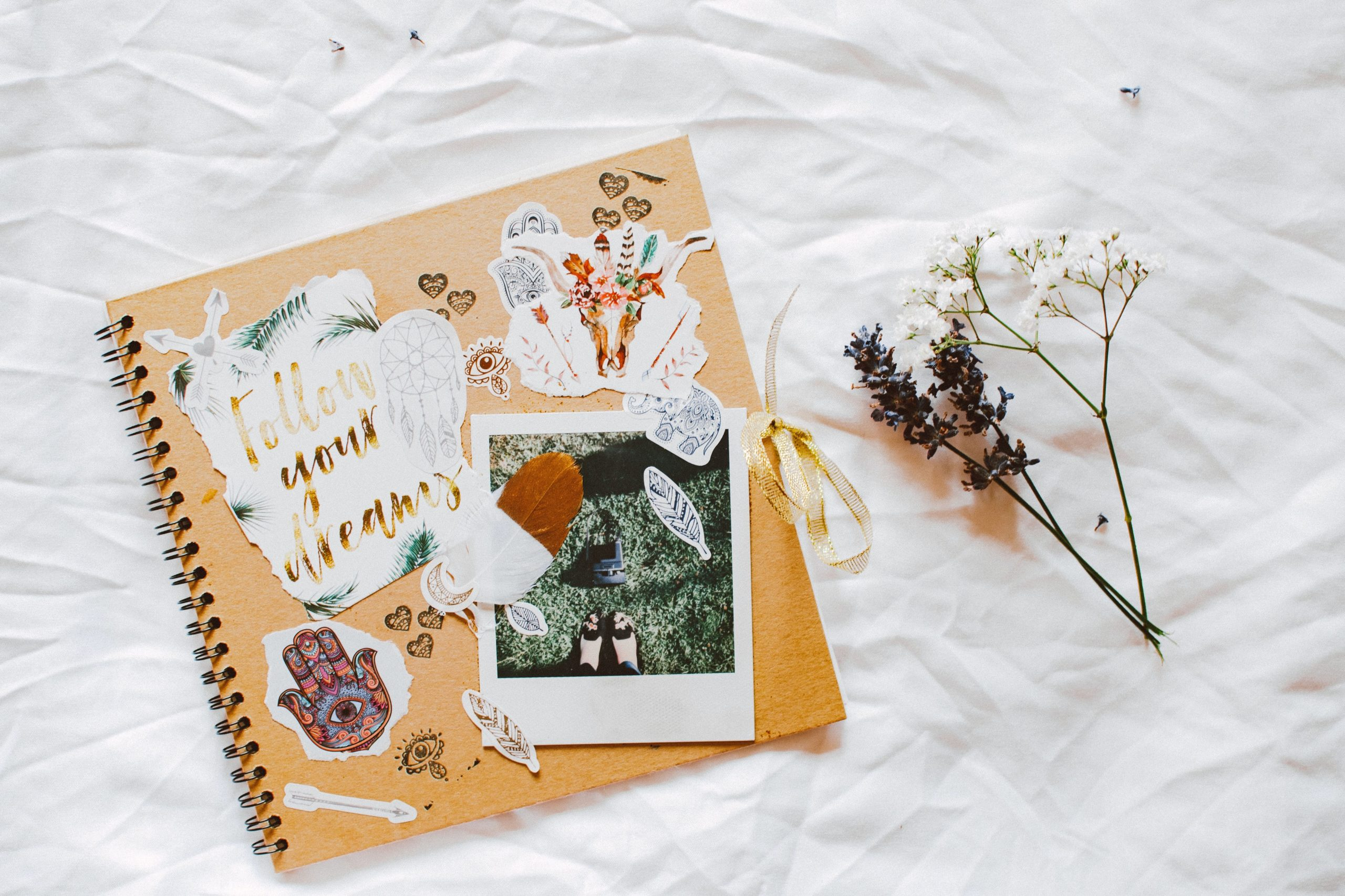 scrapbook on white textile, next to a flower. Scrapbooks are a good idea when it comes to planning events, like a wedding!