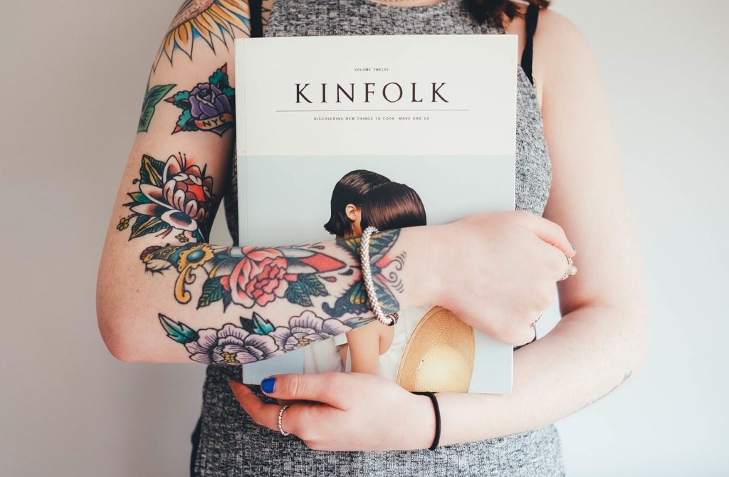 Woman with tattoos on her arm holding a book