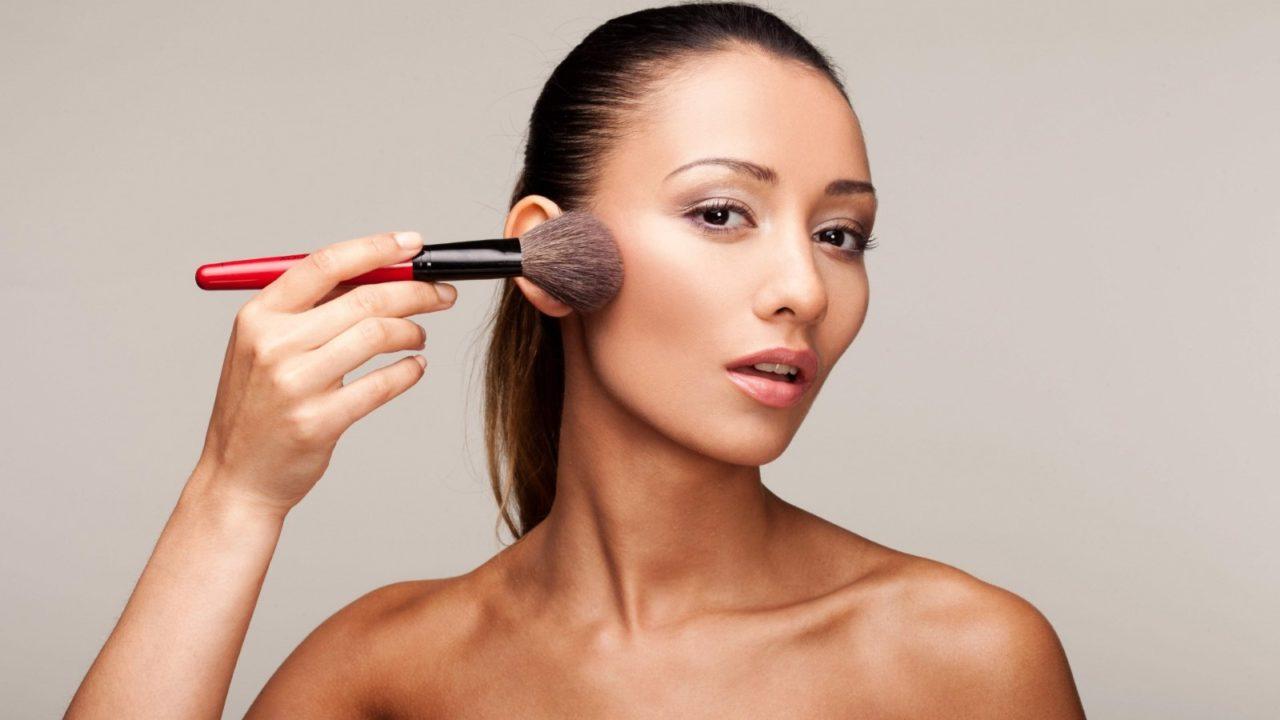 woman applying makeup with large powder brush.