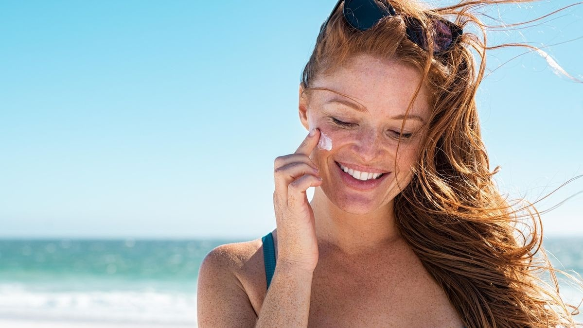 woman applying sun lotion to her cheeks, over her freckles.