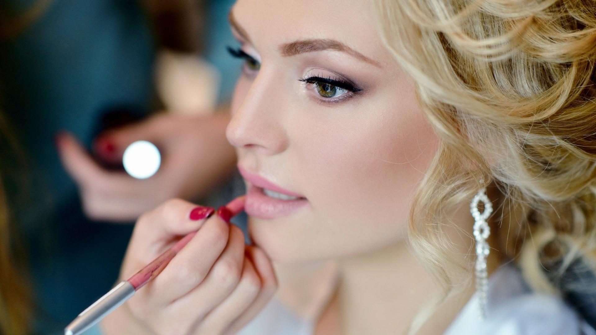 woman having her lip liner applied.