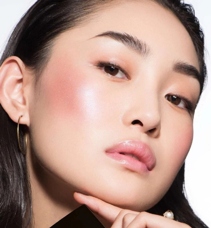 woman posed with blush on the apple of her cheeks.