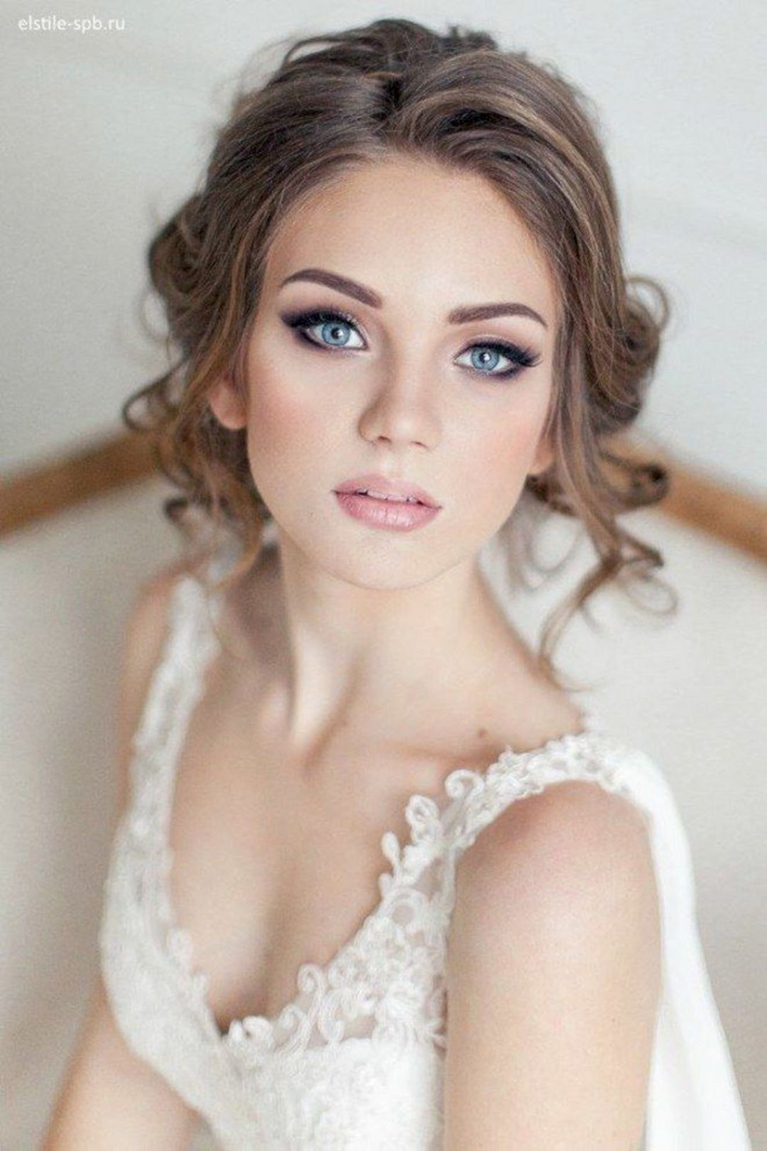 woman posing towards camera whilst wearing perfect makeup and a wedding dress.