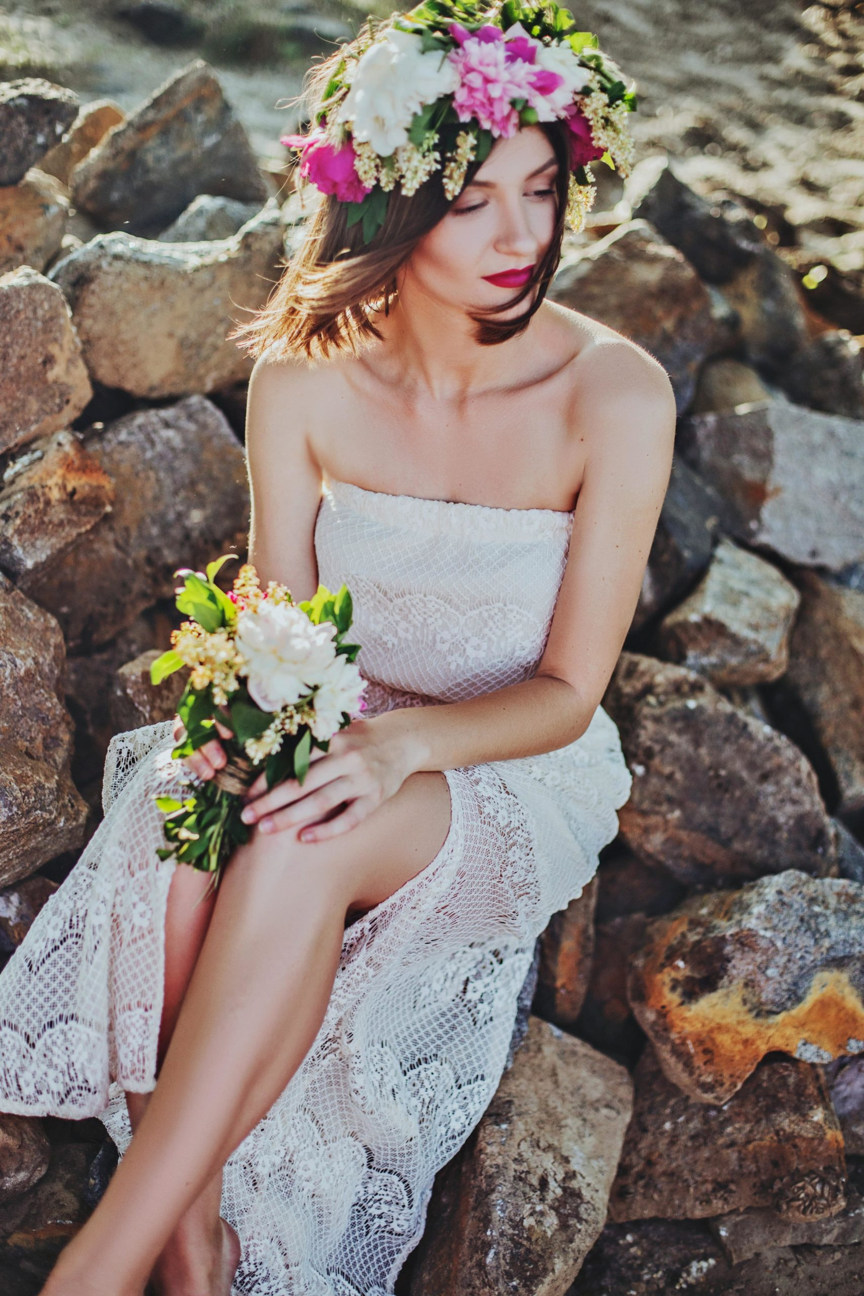 woman posing with little makeup in a wedding dress, upon rocks.
