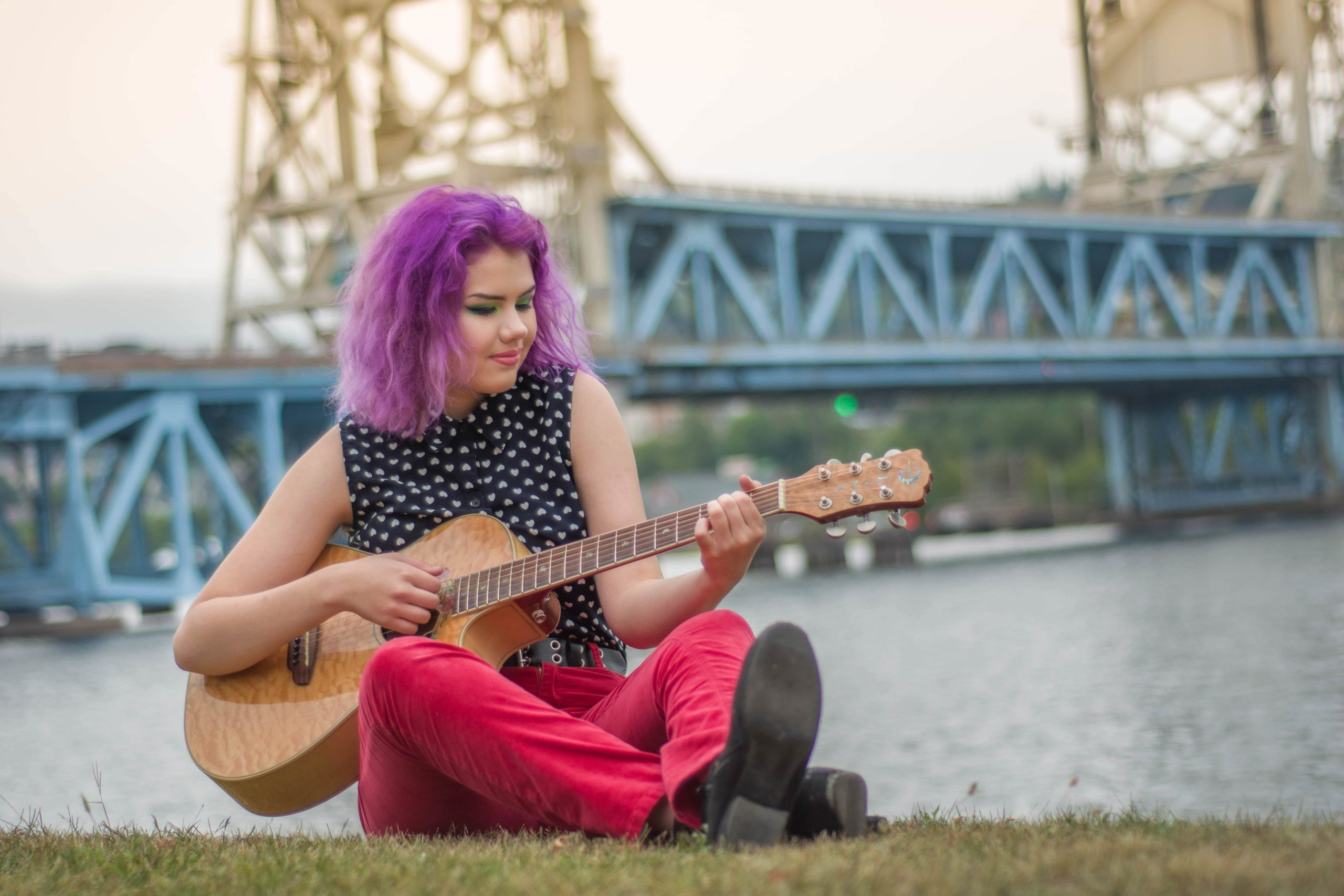 a woman playing guitar in front of a bright, with bright purple hair.