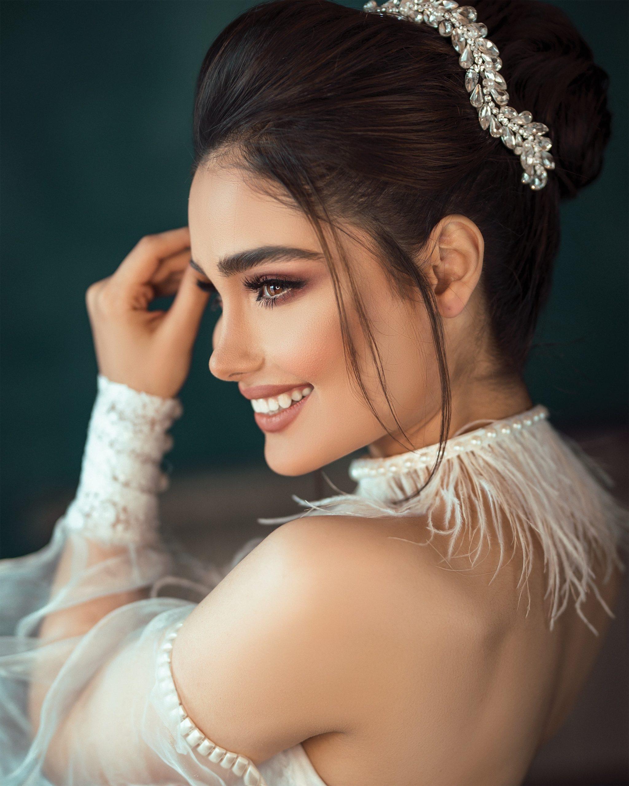 woman smiling, wearing defined makeup and tiara.