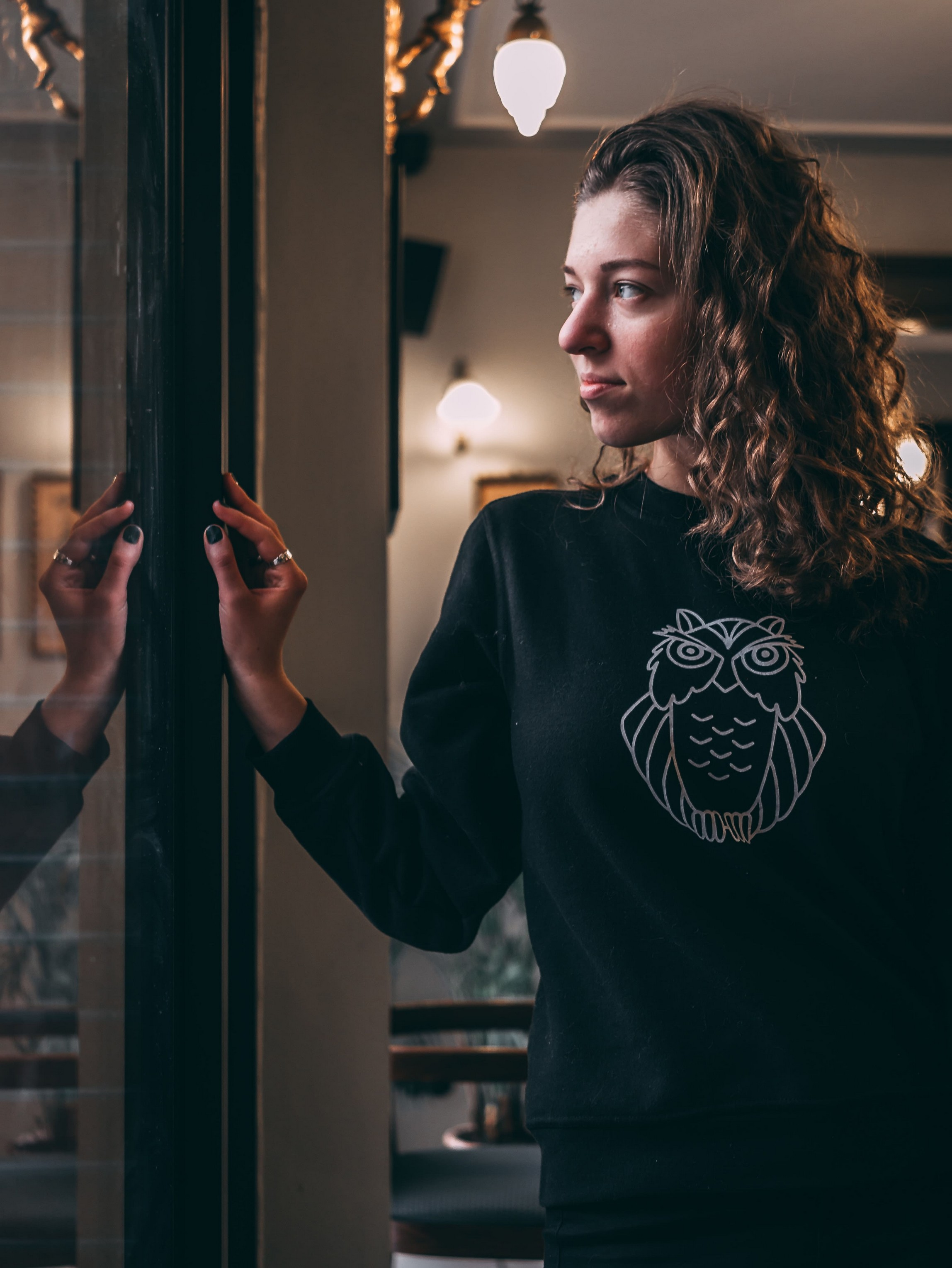 woman with curly hair stood in front of a window, whilst wearing a dark jumper with owl print.