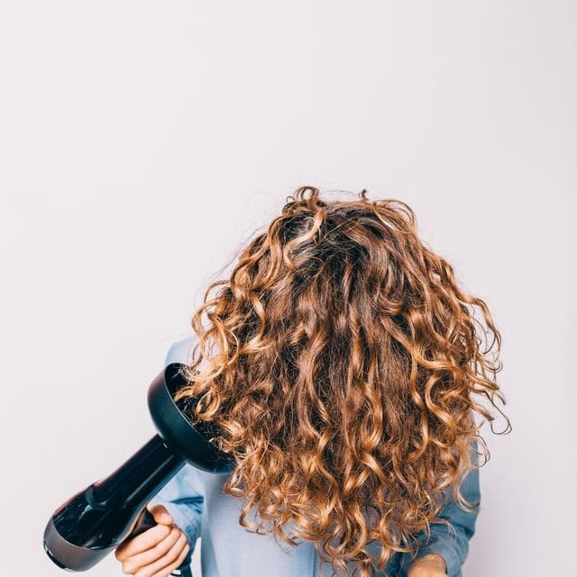 a woman using her hair diffuser, on her curly hair, with her head upside down.