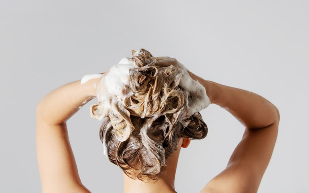 woman washing her curly hair with shampoo suds.