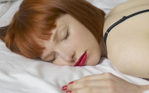 a woman lying in bed asleep with her makeup on.