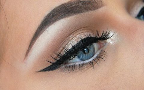 close up of woman's eyeliner with golden eyeshadow.