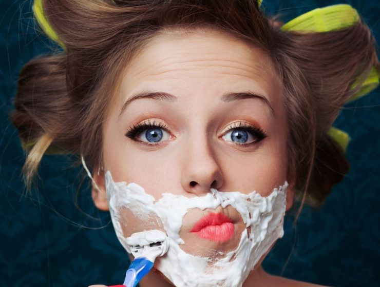 close up of a woman wearing shaving foam on her face, whilst holding a razor.